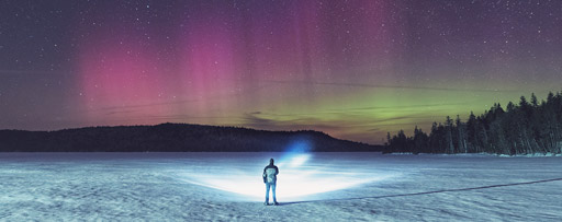 Man standing on frozen lake shining torch at shoreline