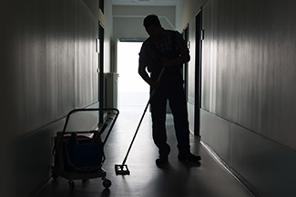 Man with broom sweeping an office corridor
