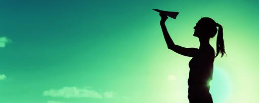 Silhouette of a woman throwing paper airplane