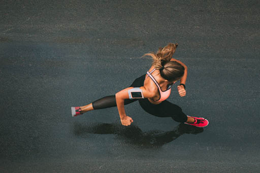 Athletic woman running along the street