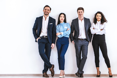 Four business people standing against a white wall