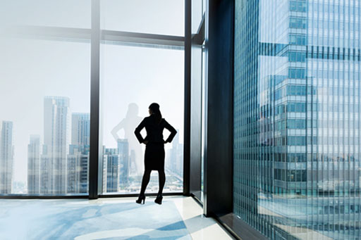 Businesswoman looking out window from office building