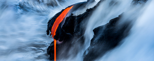Changing state of distant lava flowing off rock into wild ocean.