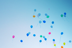 Coloured balloons floating against a blue sky