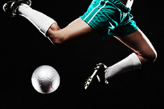 Soccer player in green uniform jumping over the ball