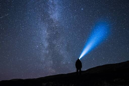 Man illuminating the night sky with a blue light