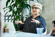 Mature female business owner leading team discussion