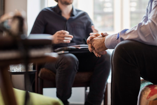 Midsection of businessmen discussing while sitting in office