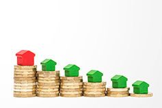 Stack of coins with green and red wooden toy houses on top