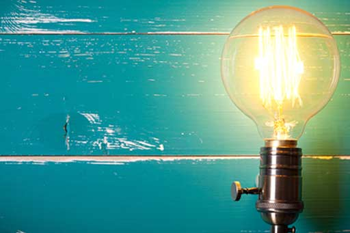 Vintage light bulb on turquoise wooden table