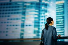Woman overlooking city skyline at night