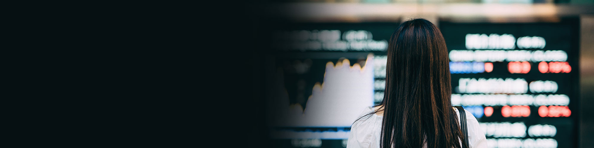 A business woman looks as stock market trading figures are displayed on screens