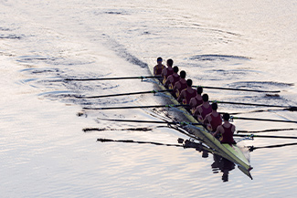 A rowing team practices on a calm lake