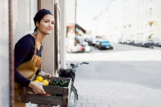 A woman with a crate full of goods at the entrance to a business