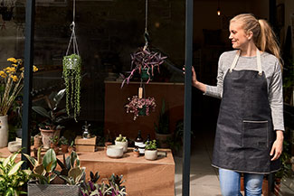 Female shopkeeper standing in plant shop doorway