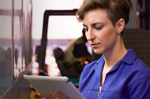 A female steel worker looks at information on a tablet computer
