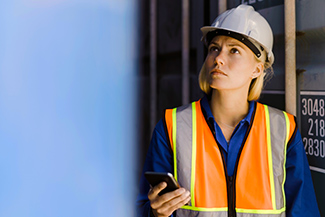 A woman in hi-vis and a hardhat inspects a site