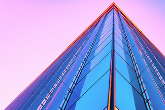 Glass building against a pink sky