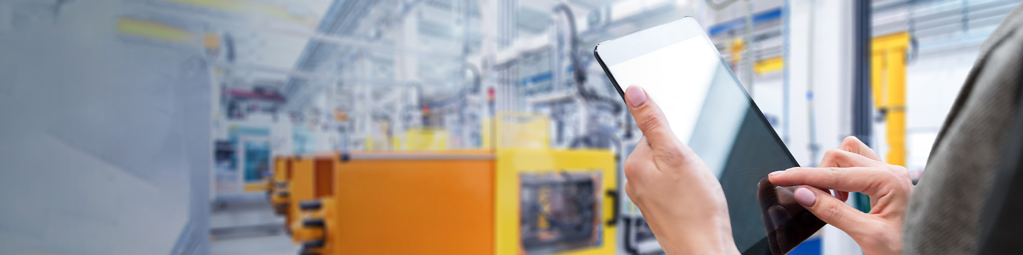 hands holding digital tablet in a manufacturing plant