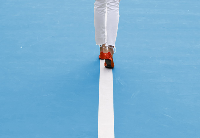 Lady walking along a white line