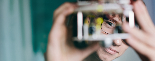Man with glasses peers through a device