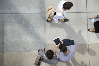 Aerial view of a meeting with people huddled around a tablet computer