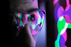 Person with goggles studying multi-coloured connected dots