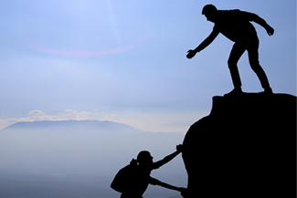 Silhouette of one man assisting another man to climb to the top of a mountain