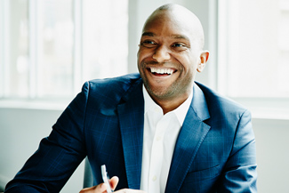 Smiling businessman in discussion at workstation