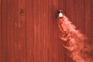 A red, dusty crop being harvested