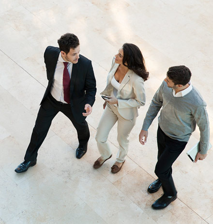 Three business people walking and talking in an office lobby