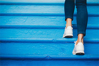 Woman wearing jeans walking up blue steps
