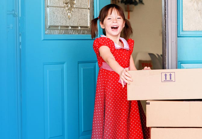 Young girl at front door with an online delivery