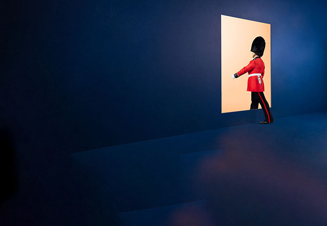 Queens guards walking through a light door
