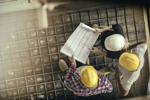 People in hardhats looking at plans