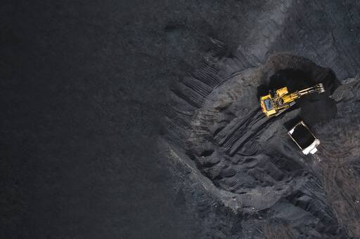 Aerial view of an open pit mine with excavator and truck