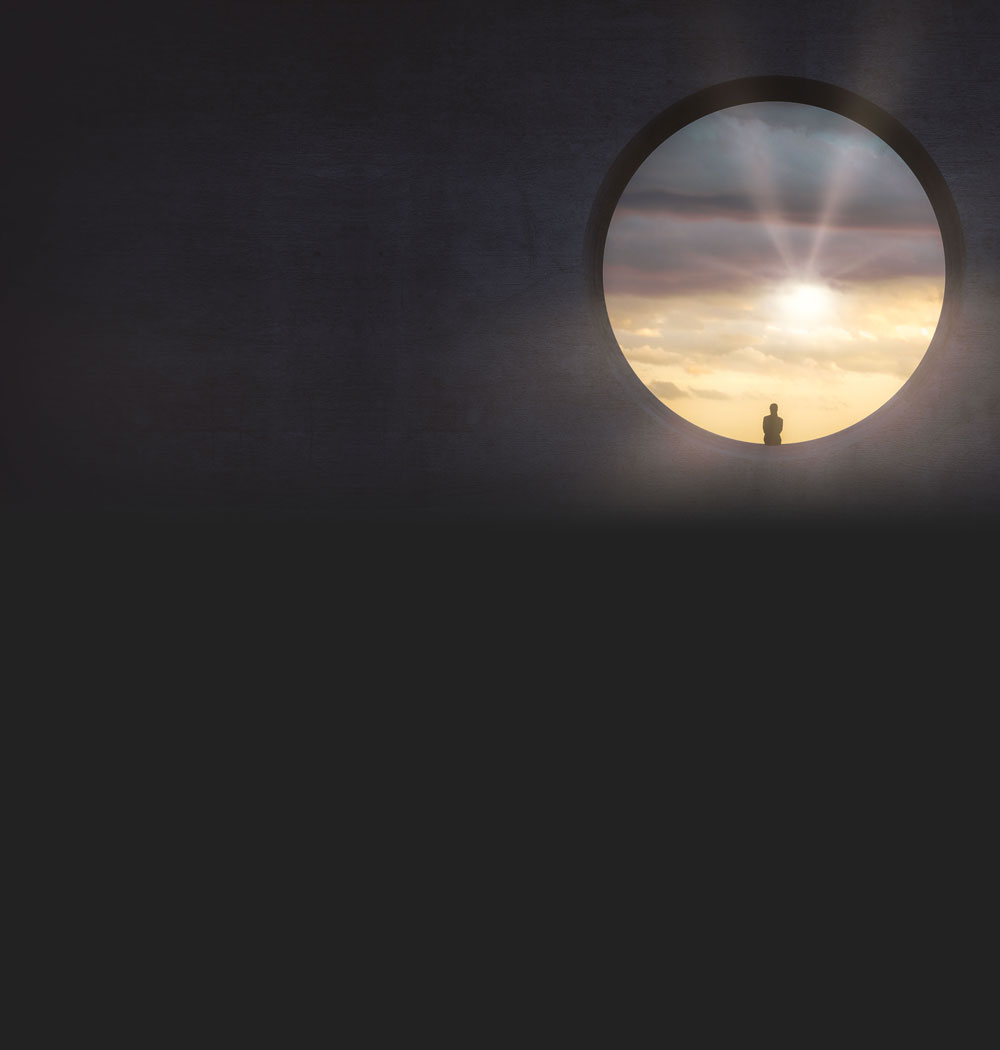 tunnel view of woman sitting in a sunny sunset background