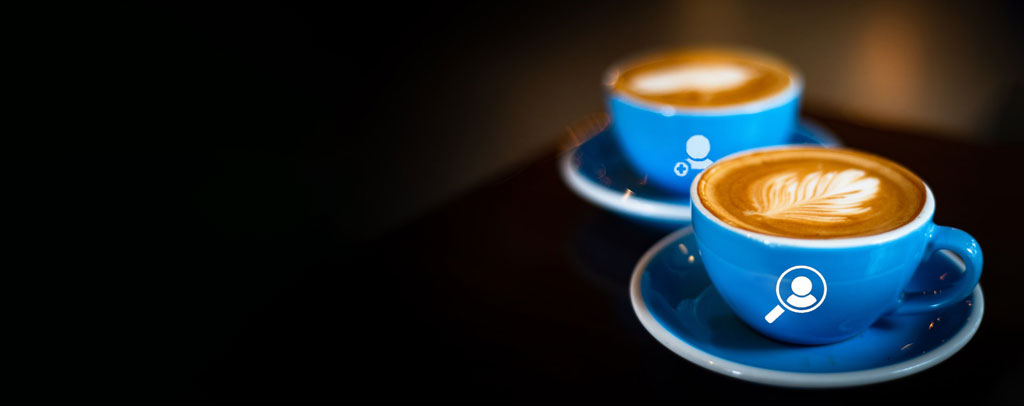 two blue coffee cups on green background