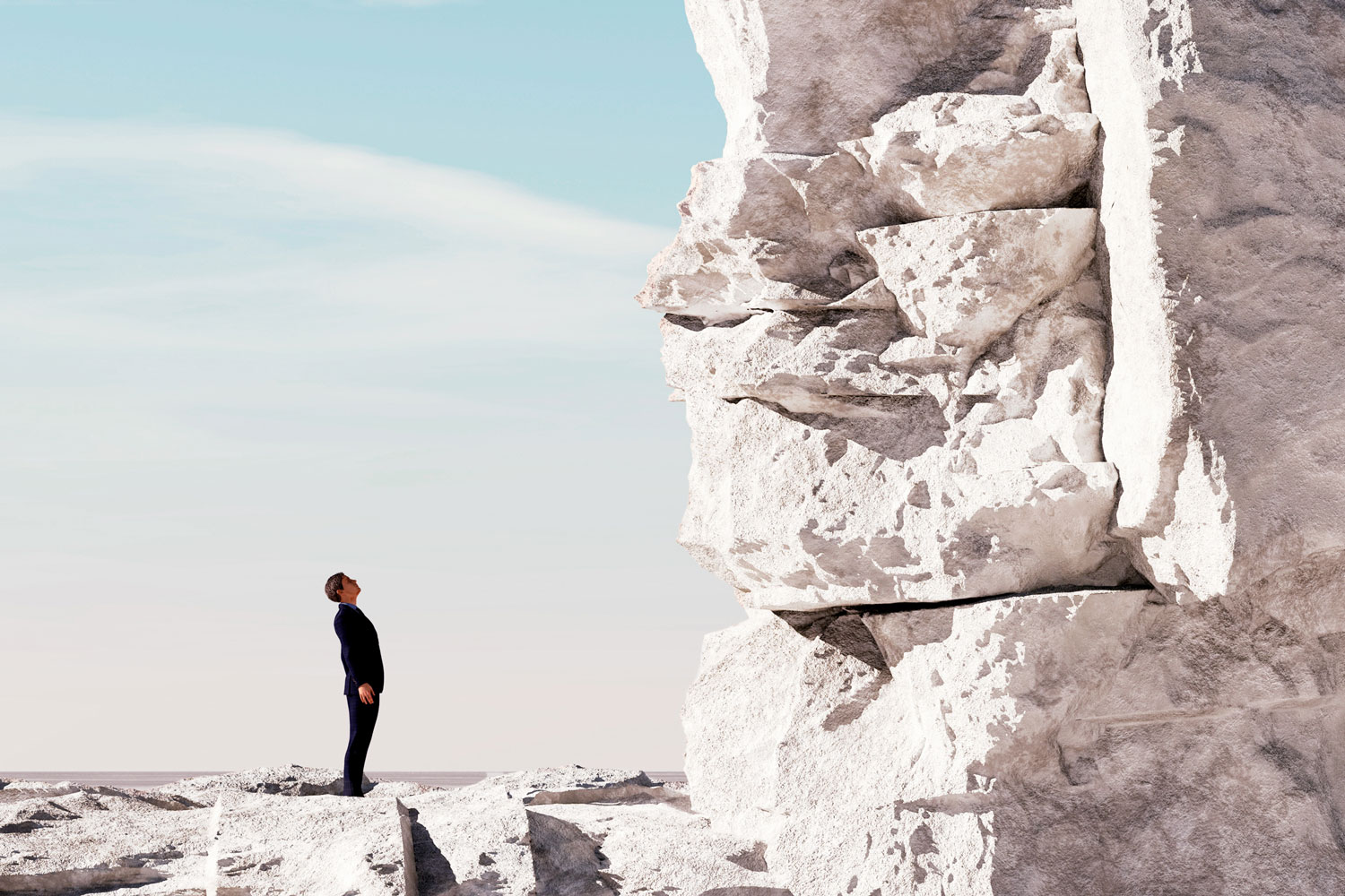 man dressed in black looking at top of beach cliff