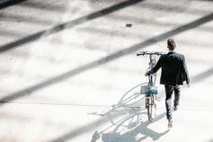 Man pushing a bicycle over shadow of a building
