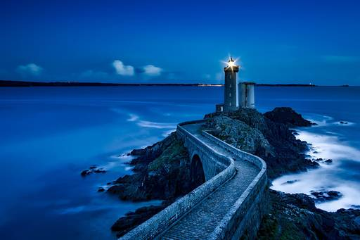 Lighthouse in the night against backdrop of sea