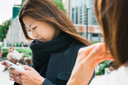 woman using mobile in street