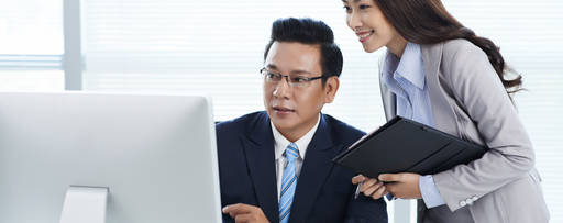 businessman and his assistant looking at computer screen