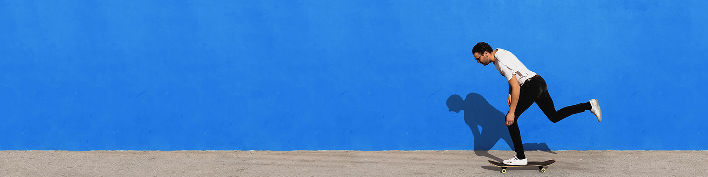 Guy on skateboard in front of blue wall