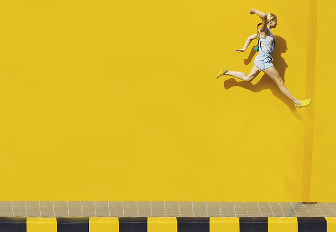Woman jumps infront of yellow wall