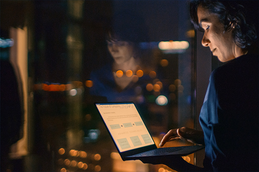 Woman looks at her laptop and is reflected in the window
