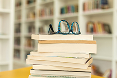 Glasses on top of a pile of books