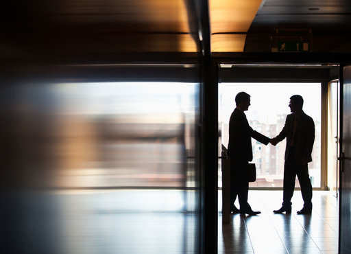 businessmen shaking hands in a corridor