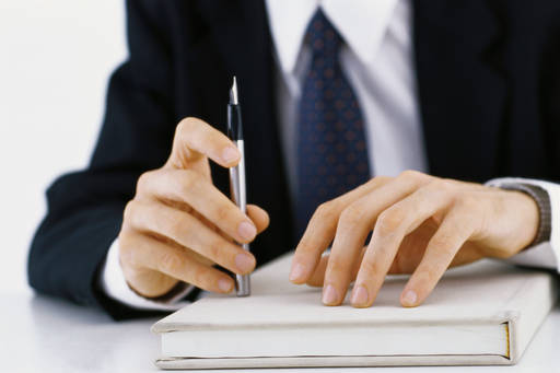 Businessman sitting at a table holding a pen in one hand and resting his other hand on a book