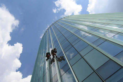 Worm's eye view of window cleaners on the side of a tall building